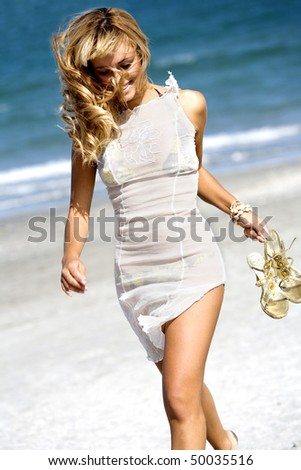 Sensual happy blonde woman running windblown on the beach - stock photo