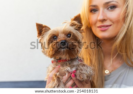 Sensual happy blonde woman sitting on wooden bench with her dog.