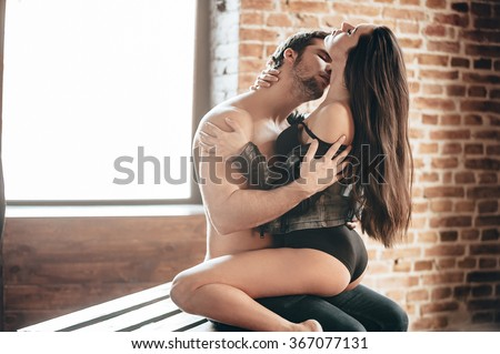 Sensual kiss. Side view of beautiful young loving couple kissing and hugging while sitting on wood pallet and in front of the brick wall  - stock photo