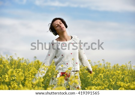 Sensual lady listening to music in headphones and dancing in a canola field - stock photo