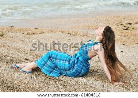 sensual longhaired young woman posing on the beach - stock photo