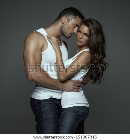 Sensual man hugging beautiful young woman - stock photo