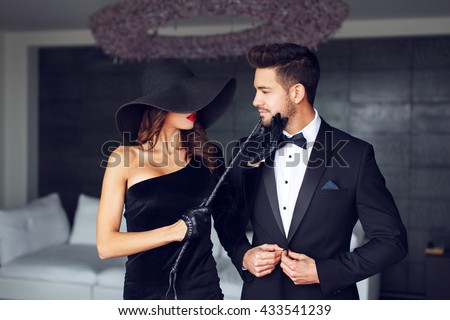 Sensual milf woman in black hat and whip holding young macho lovers chin - stock photo