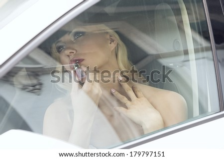 sensual modern blonde female sitting in a white car with elegant style and putting on lipstick. adjusting her make-up - stock photo