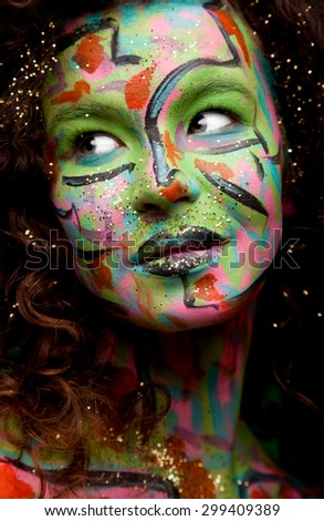Sensual mysterious woman with green, pink, red face paint  and curly hair - stock photo