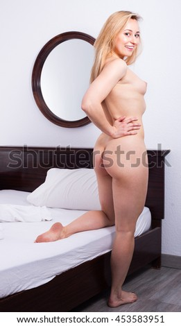 Sensual naked longhaired blond young  woman posing in bedroom - stock photo