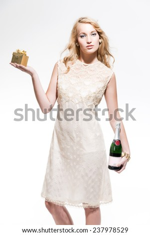 Sensual new year's eve fashion woman with blonde hair wearing gold dress. Holding a golden present and glass of champagne. Isolated against white. - stock photo
