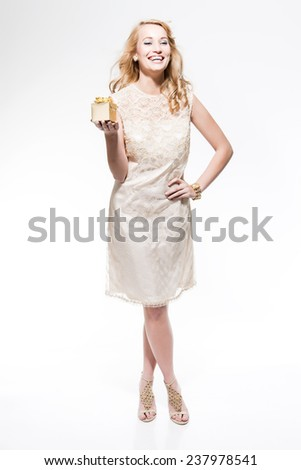 Sensual new year's eve fashion woman with blonde hair wearing gold dress. Holding a golden present. Isolated against white. - stock photo