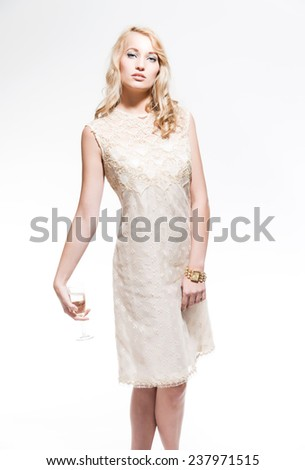 Sensual new year's eve fashion woman with blonde hair wearing gold dress. Holding glass of champagne. Isolated against white. - stock photo