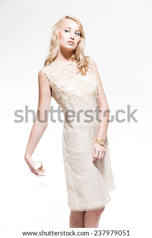 Sensual new year's eve fashion woman with blonde hair wearing gold dress. Holding glass of champagne. Isolated against white.
