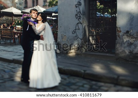 Sensual newlywed couple hugging in old italian street - stock photo