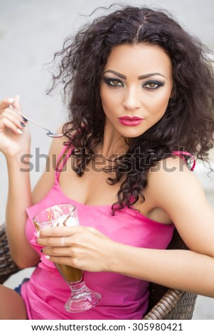 Sensual playful brunette lady with curly hair and bright makeup in pink clothes eating cold dessert of ice cream and coffee glissade from glass with spoon, vertical picture - stock photo