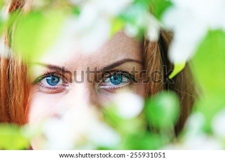 Sensual portrait of a spring woman, beautiful face, close up on blue eyes, female enjoying cherry blossom, dreamy girl with white fresh flowers outdoor Seasonal nature, tree branch and natural beauty - stock photo