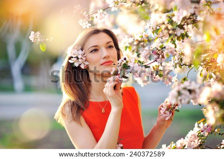 Sensual portrait of a spring woman, beautiful face female enjoying cherry blossom, dreamy girl with pink fresh flowers outdoor, seasonal nature, tree branch and glamorous lady. - stock photo