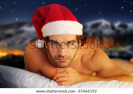 Sensual portrait of a young shirtless male model laying on pillow against fantasy winter background - stock photo