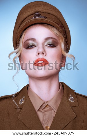 Sensual portrait of an elegant young blond female army recruit standing with her head tilted back looking at the camera with parted lips against a blue background - stock photo