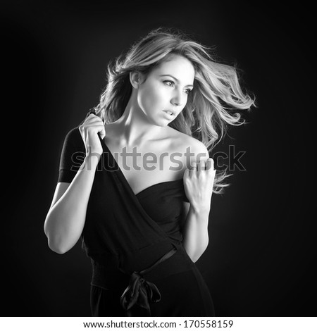 Sensual portrait of blonde woman on black background. Black and white image.
