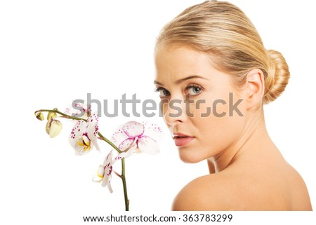Sensual portrait of nude woman with orchid flower - stock photo