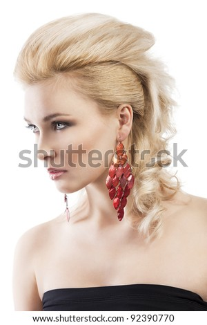 sensual portrait of very attractive blond woman with creative hair style and big fashion red earring with black top, she is turned three quarters and looks in front of her - stock photo