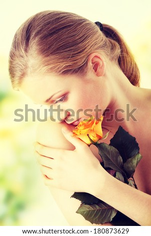 Sensual portrait of young nude sexy blond woman with orange rose  - stock photo