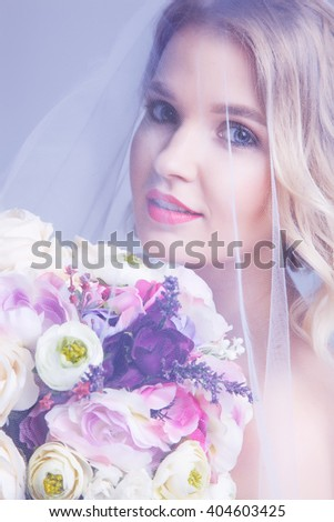 Sensual portrat of young beautiful bride holding flower bouquet under veil.