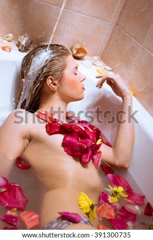 sensual relaxation:  attractive happy smiling blond beautiful young woman relaxing taking milk shower with flower petals with eyes closed portrait picture - stock photo