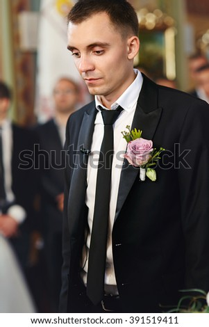Sensual romantic handsome groom at wedding ceremony in church