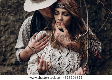 Sensual romantic man in cowboy hat hugging a beautiful gypsy brunette woman from behind, while she is holding a berry tree branch closeup