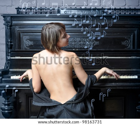 Sensual semi-dressed woman performing romantic music on piano, music symbols - stock photo