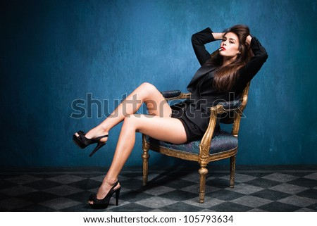 sensual smoking young woman in black tuxedo and high heel shoes sit on armchair in blue room with tiled floor