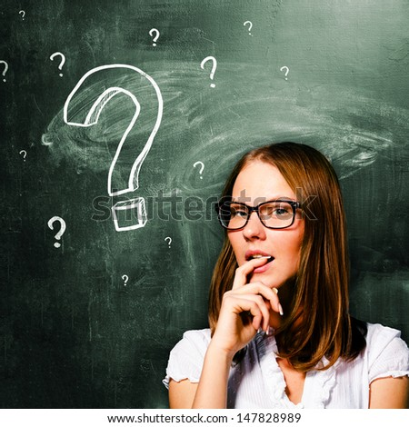 sensual student woman is standing with chalk board behind her - stock photo