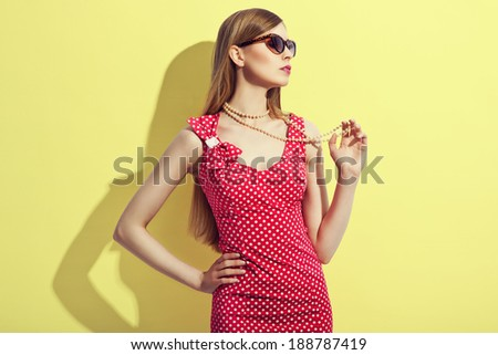 sensual summer girl in sunglasses over yellow background  - stock photo