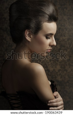 sensual sweet portrait of beauty woman in old fashion style , looking down and showing her shoulder