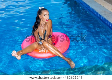 Sensual tanned woman with long legs and ponytail swims in big pink inflatable circle in swimming pool. She looks to the camera