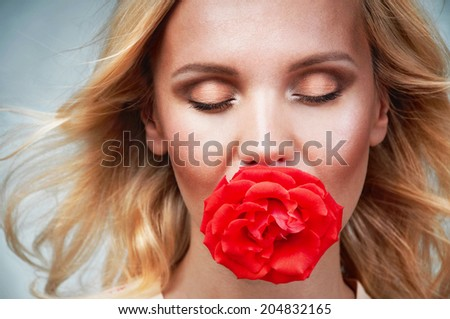 sensual tender delicate young woman portrait with breeze hair and rose in mouth, enjoyment concept on vintage background - stock photo