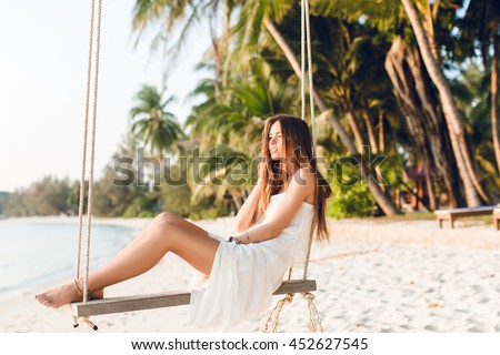 Sensual tender girl sitting on a swing wearing white dress. Girl has her eyes closed. She has long dark hair. She has bracelets on her arm and leg. The swing is on the beach with green palms. - stock photo