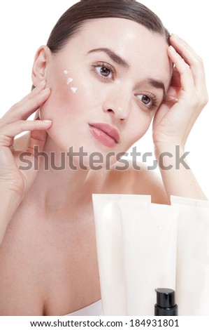 Sensual woman applying cosmetic cream treatment on her face. Skin care concept.  - stock photo