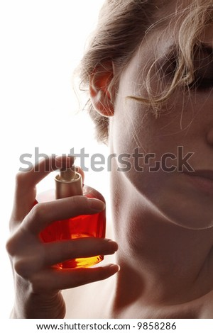 sensual woman applying perfume on her body, bright red perfume bottle - stock photo