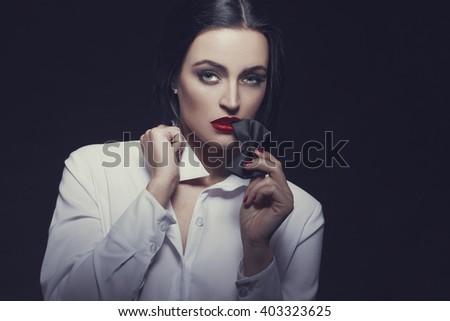 Sensual woman bite tux at night, desire, retro style - stock photo