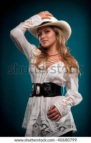 Sensual woman cowgirl posing with hat and smiling. - stock photo