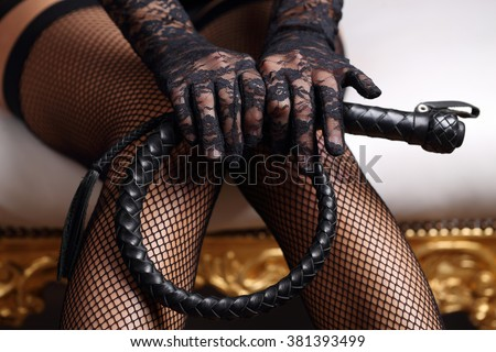 Sensual woman in black lingerie and leather whip - stock photo