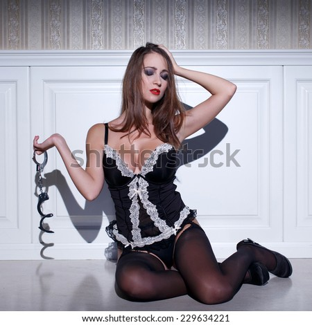 Sensual woman in lingerie sit on floor holding handcuffs, desire - stock photo