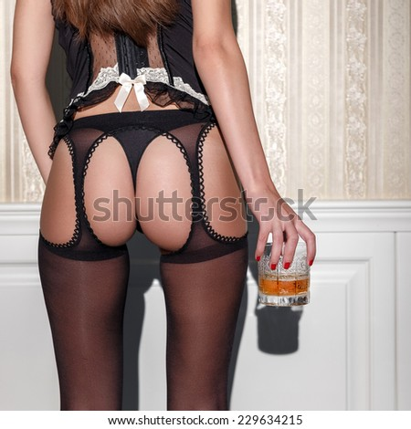 Sensual woman in stockings holding glass of whiskey - stock photo