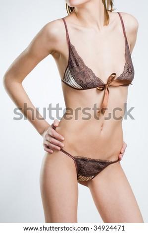Sensual woman in stylish brown lingerie, studio shot - stock photo