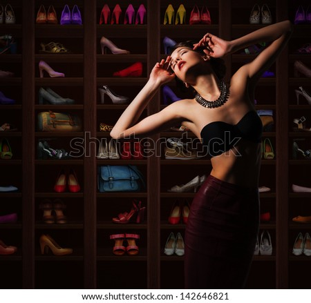 Sensual Woman in Wardrobe with Plenty of Footwear - stock photo