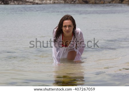 Sensual woman in wet shirt crawling in the sea by the seaside - stock photo