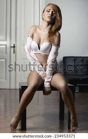 Sensual woman in white bra and pink shirt is sitting on the table in sexy pose. She has got nice make up and readhead hair. - stock photo