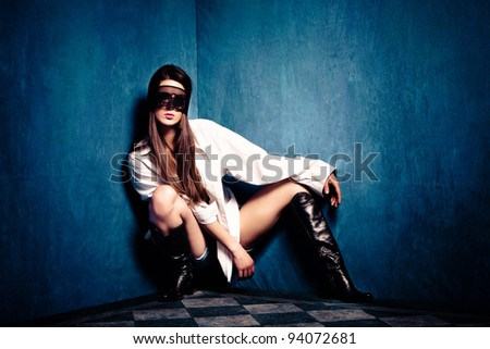 sensual woman in white shirt and lace over eyes in old grunge room, small amount of grain added - stock photo