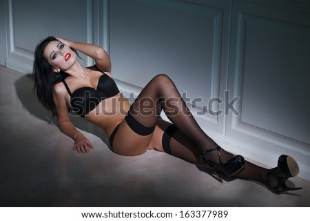 Sensual woman laying on the floor at night - stock photo