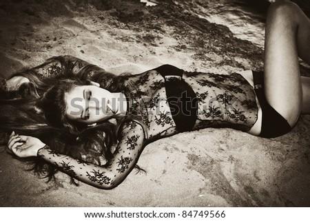 sensual woman lie on beach and smoking - stock photo